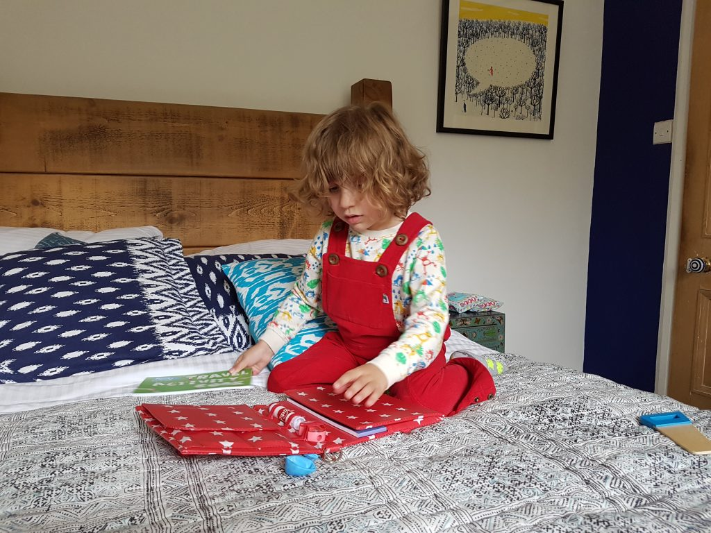 a small boy sitting on a bed with activity books family staycation