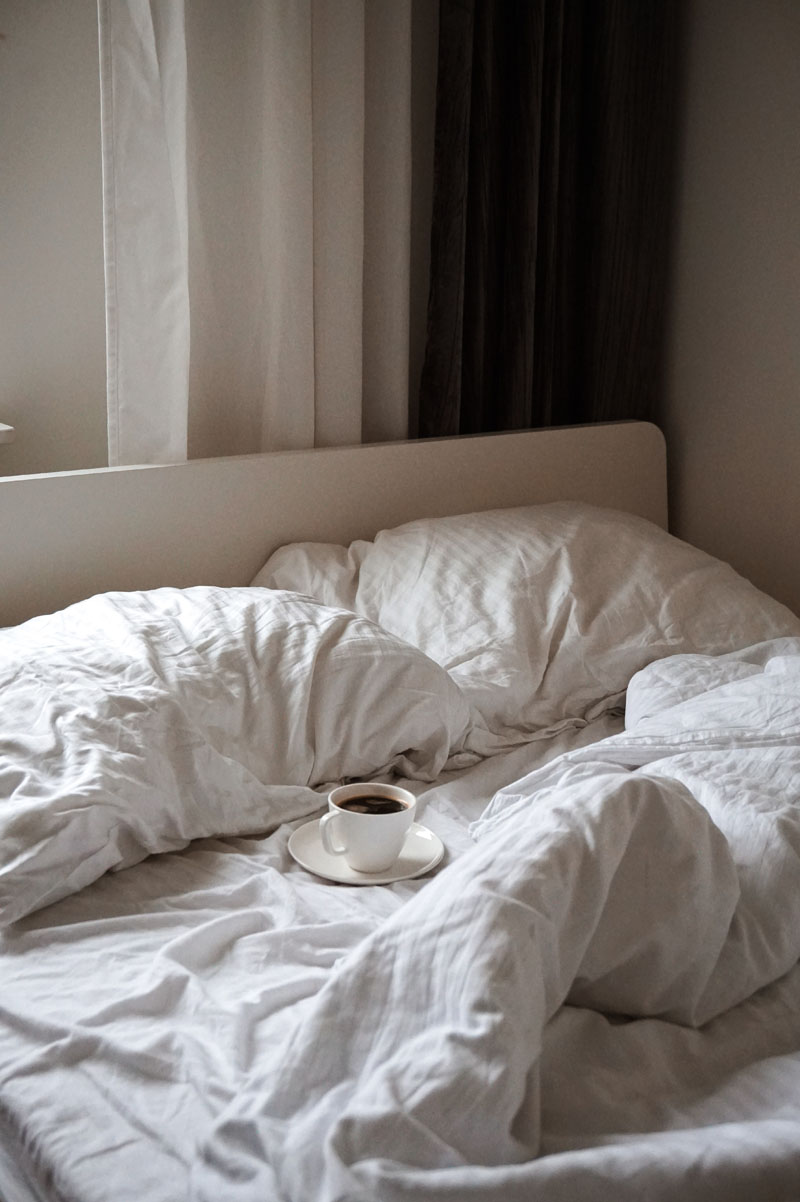 unmade bed with coffee cup resting on it