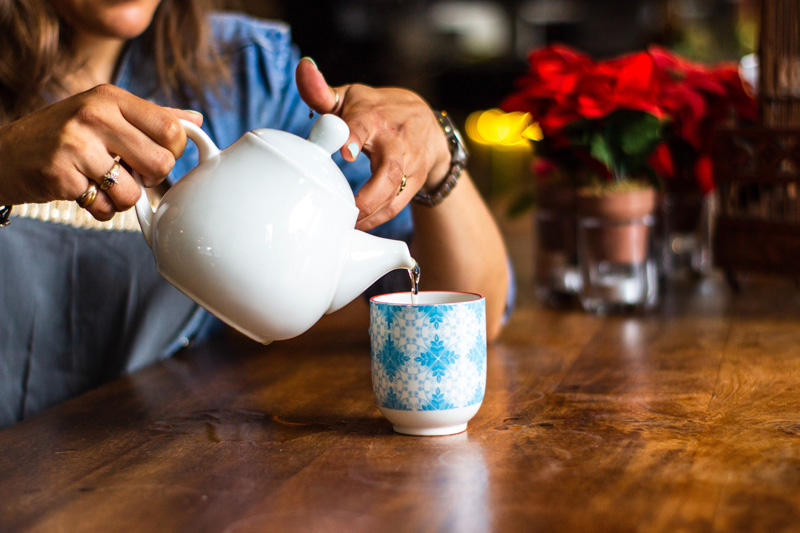 close up of woman pouring tea from a pot ways to ration spoons spoonie mum