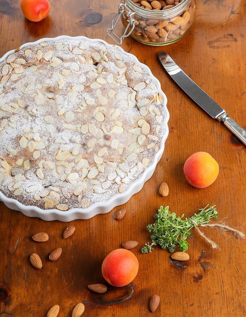 flatlay of lemon balm with a peach and almond tart