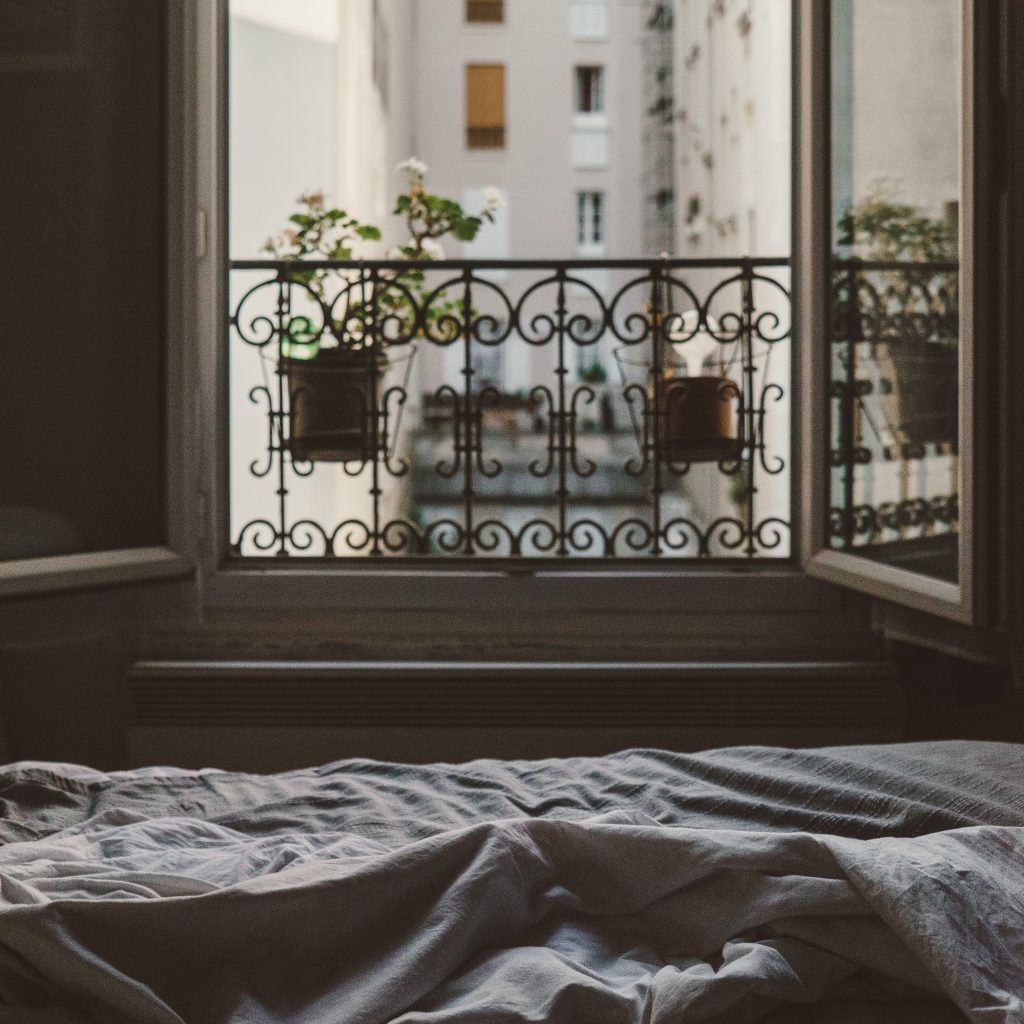 veiw from a bed through a Parisian apartment window catching the morning light