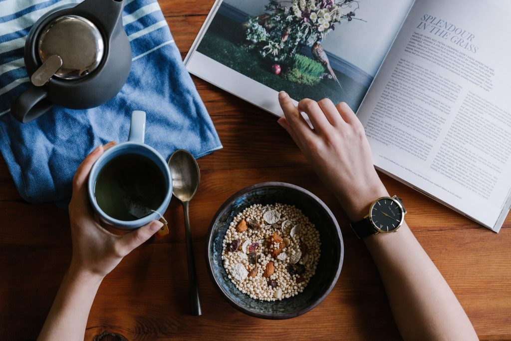 a flatlay image of a morning routine table with oats coffee and a magazine