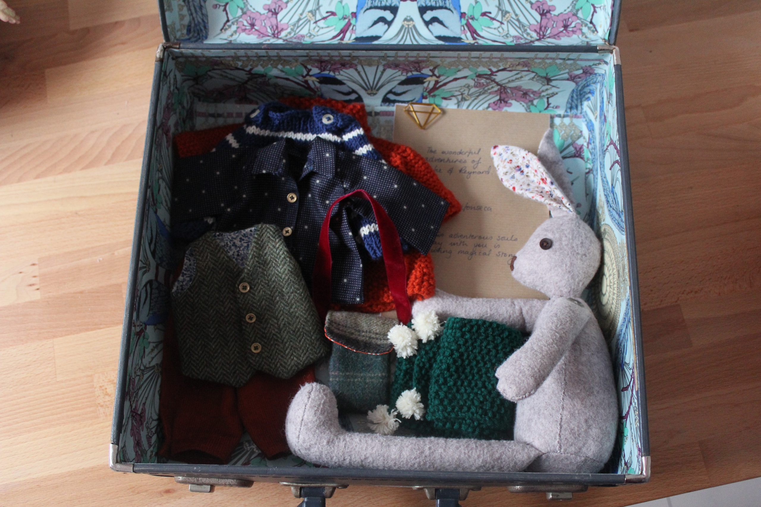 a handmade rabbit in an upcycled   vintage suitcase with tiny handmade clothes