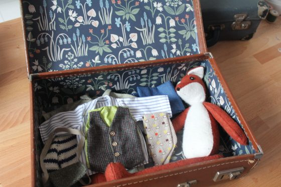 handmade fox and tiny clothes in a vintage suitcase