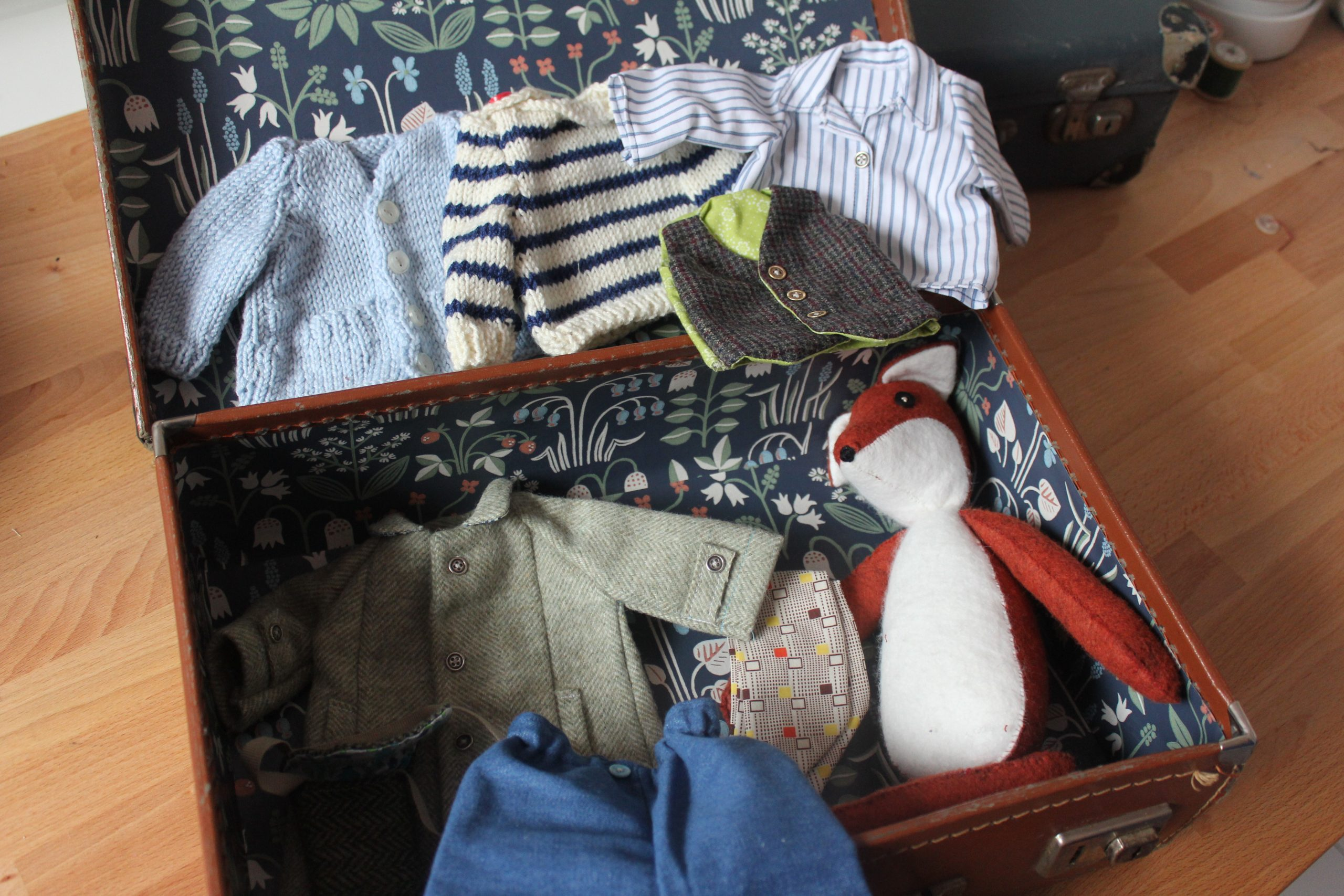 a handmade fox toy in an old suitcase filled with tiny clothes for him to wear
