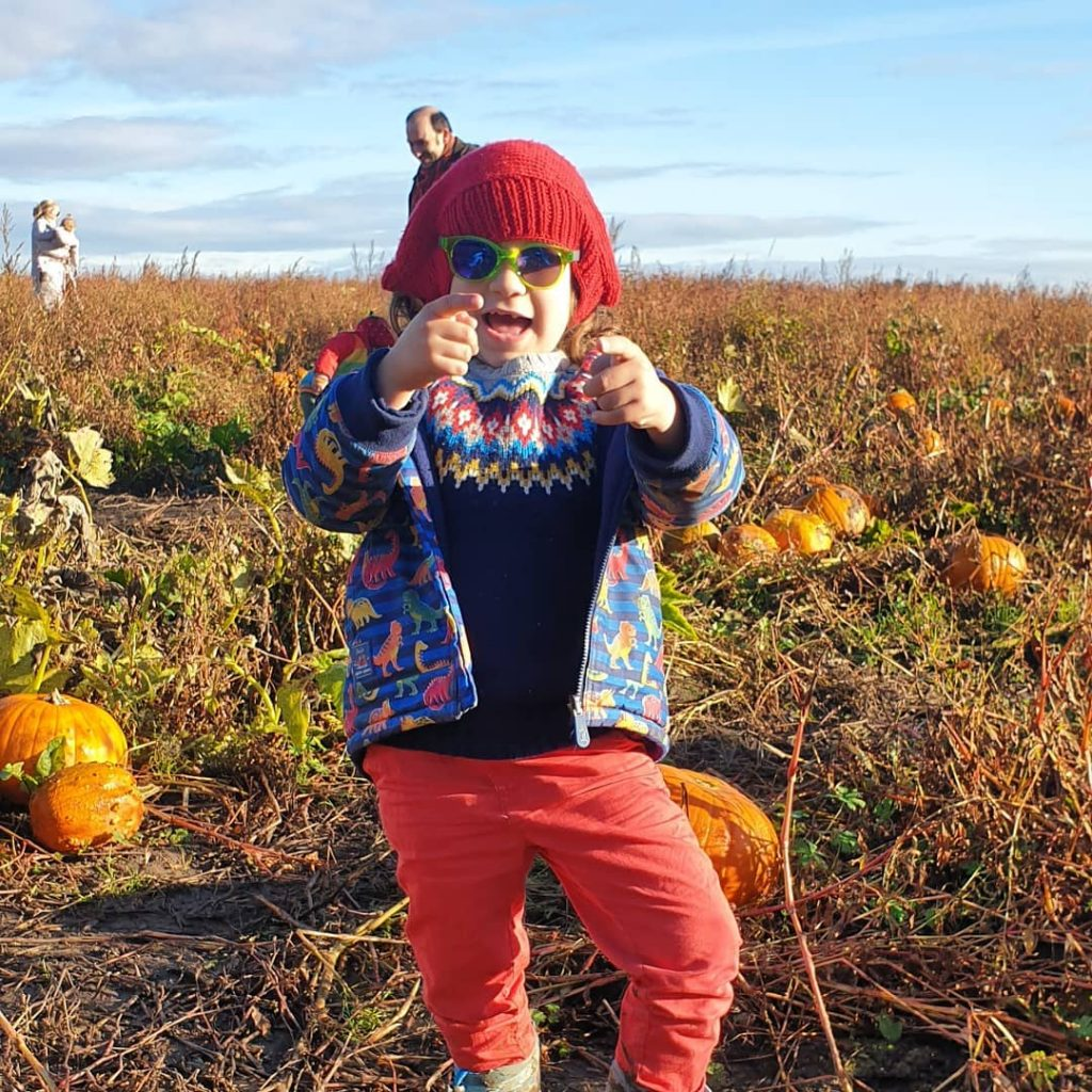 cute kid being silly in a pumpkin patch